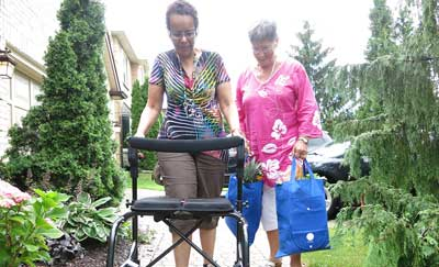 Woman with a walker being assisted walking up the driveway by a caregiver.