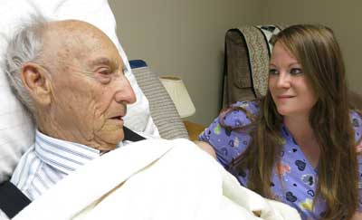 Elderly man lying in bed being cared for by hospice worker.