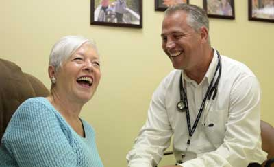 Senior woman laughing during check up with a nurse in a home setting.