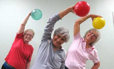 Three elderly women holding exercise balls stretching in a gym setting.